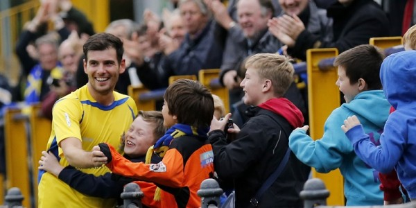 Graeme Montgomery celebrates scoring the first goal of the game with a group of young Saints fans