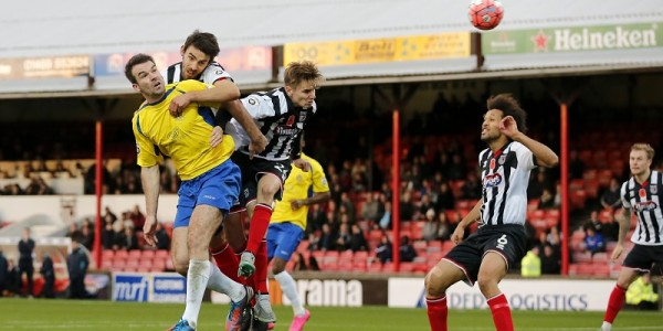 Ben Martin directs his header towards goal under pressure from the Grimsby defense