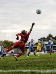 Louie Theophanous looks on as Tom Lovelock tries to stop the ball hitting the back of the net