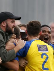 The Saints players and supports celebrate the opening goal of the game