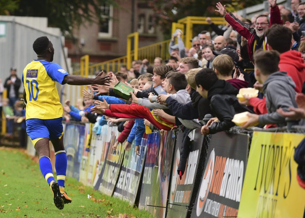 Rhys Murrell-Williamson celebrates with young fans behind the goal