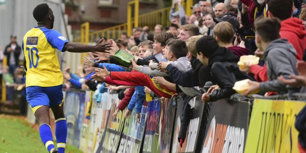 Rhys celebrates with the young fans behind the goal