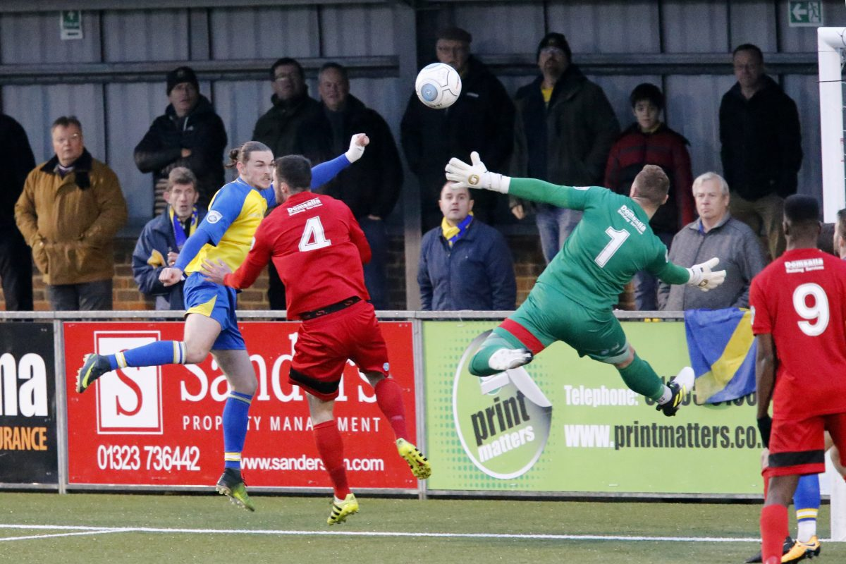 Tom Bender heads the ball across a crowded Eastbourne area