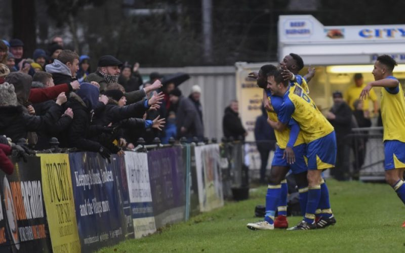 Percy celebrates his goal with players and fans